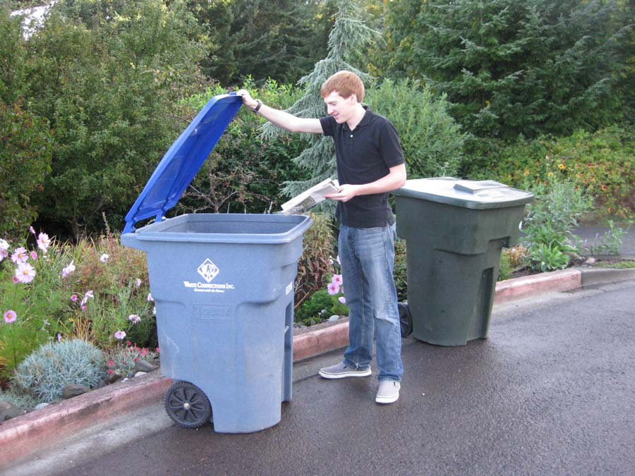 A young man putting recyclables into a blue recycling container.