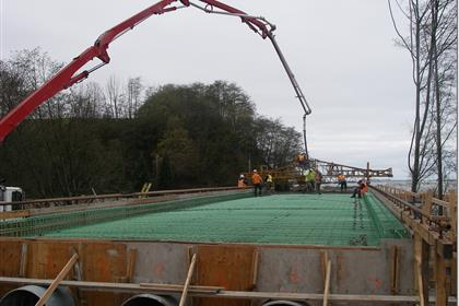 Workers constructing and pouring the bridge deck.